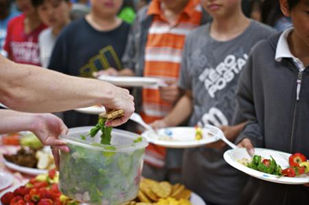 Food being served at a potluck lunch.