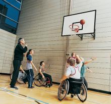 Students in wheelchairs with other students and teacher taking part in a phys. ed class.