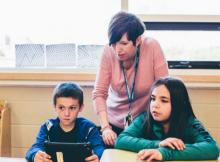 Teacher with two students in classroom looking at a tablet