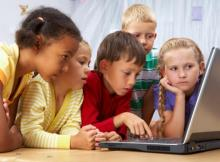group of four young children looking at laptop